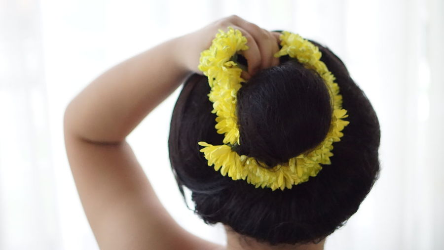 Close-up of woman holding yellow leaf