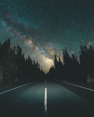 Road Amidst Trees Against Sky At Night