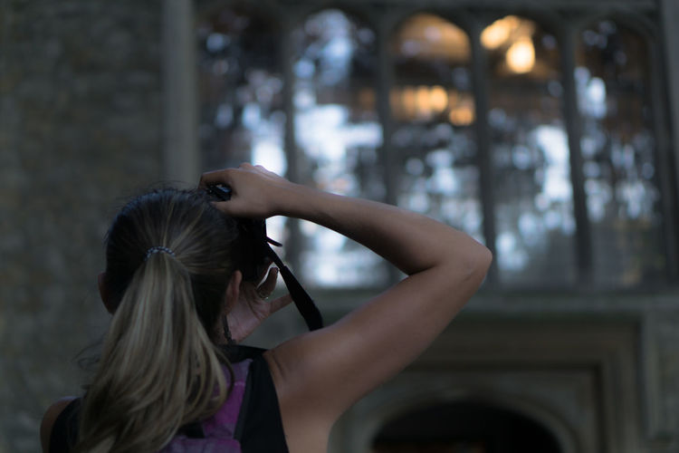 Rear View Of Woman Photographing Through Camera In Historic Building