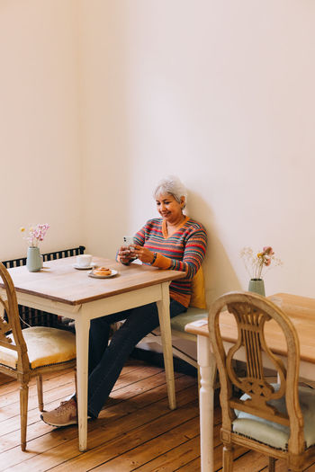Woman sitting on chair by table at home