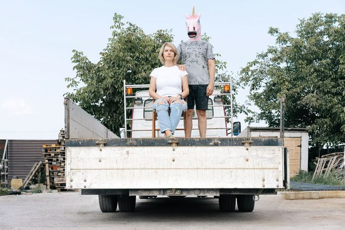 Family Portrait Unicorn Unicorn Head Men Full Length Sitting Tree Blond Hair Front View Women Sky Vehicle Trailer Trucking Semi-truck Commercial Land Vehicle Loading Dock Pick-up Truck Cargo Container Truck Posing Be Brave