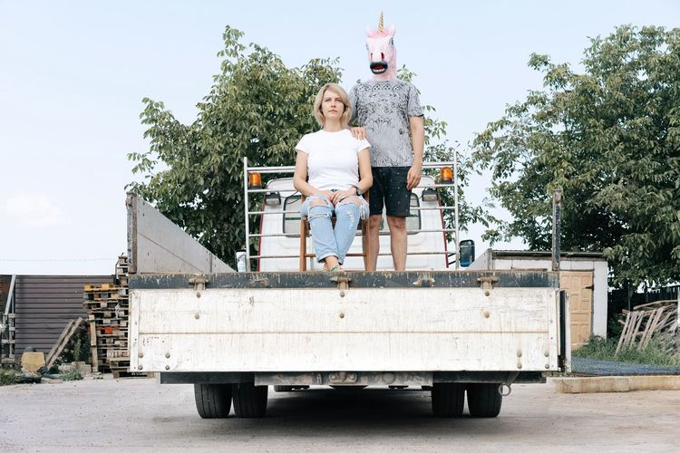 Man wearing horse mask standing by woman in truck