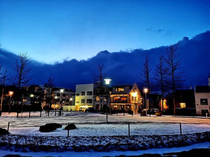 Snow covered illuminated buildings against sky at dusk