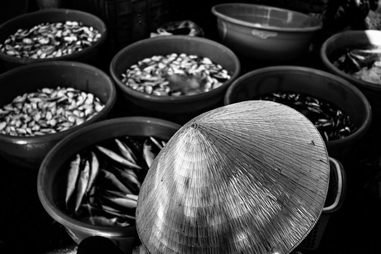 High angle view of asian style conical hat against fish in container for sale