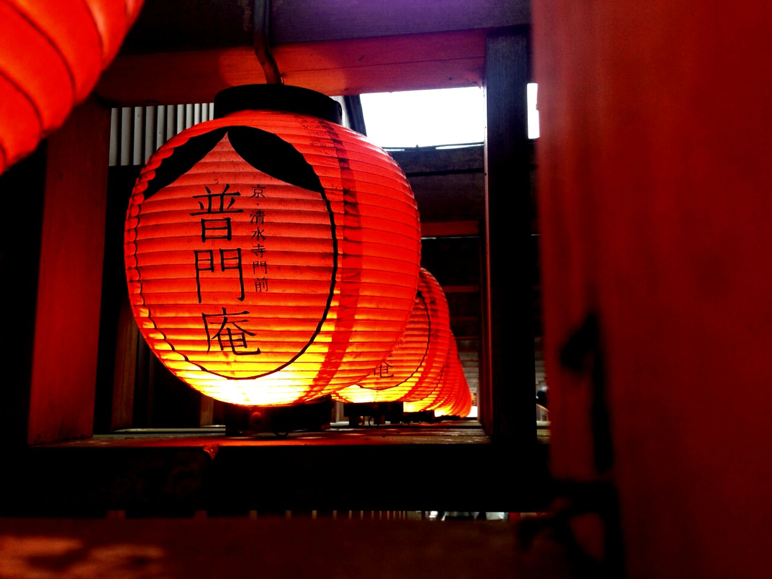 indoors, red, illuminated, orange color, built structure, hanging, architecture, window, lighting equipment, no people, low angle view, circle, lantern, arts culture and entertainment, home interior, close-up, geometric shape, pattern, glass - material, design