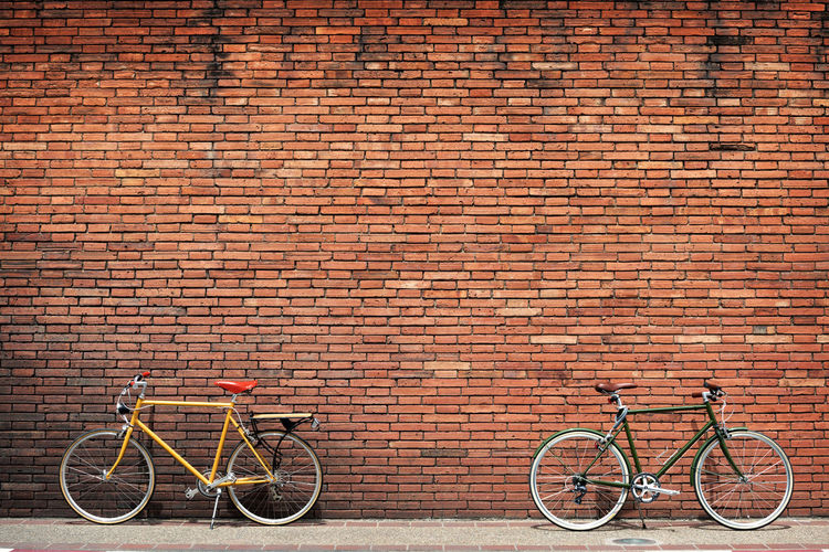 Bicycles parked against brick wall