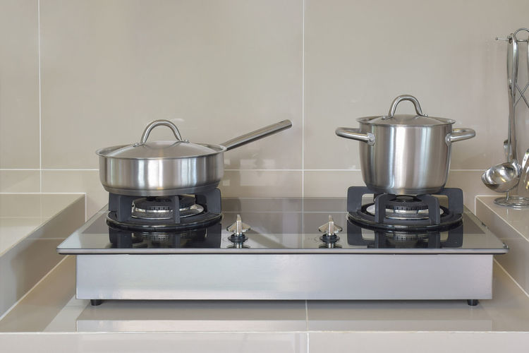 stainless pots in modern kitchen Kitchen Domestic Room Domestic Kitchen Home Household Equipment Stove Indoors  Appliance Kitchen Utensil Burner - Stove Top Metal Saucepan No People Steel Home Interior Tile Stainless Steel  Domestic Life Cooking Pan Close-up Preparation  Silver Colored Gas Stove Burner Preparing Food Alloy