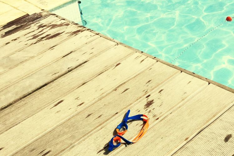 High Angle View Of Swimming Goggles On Floor By Pool