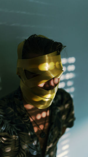 Close-up of man with yellow adhesive tape rolled on face against wall