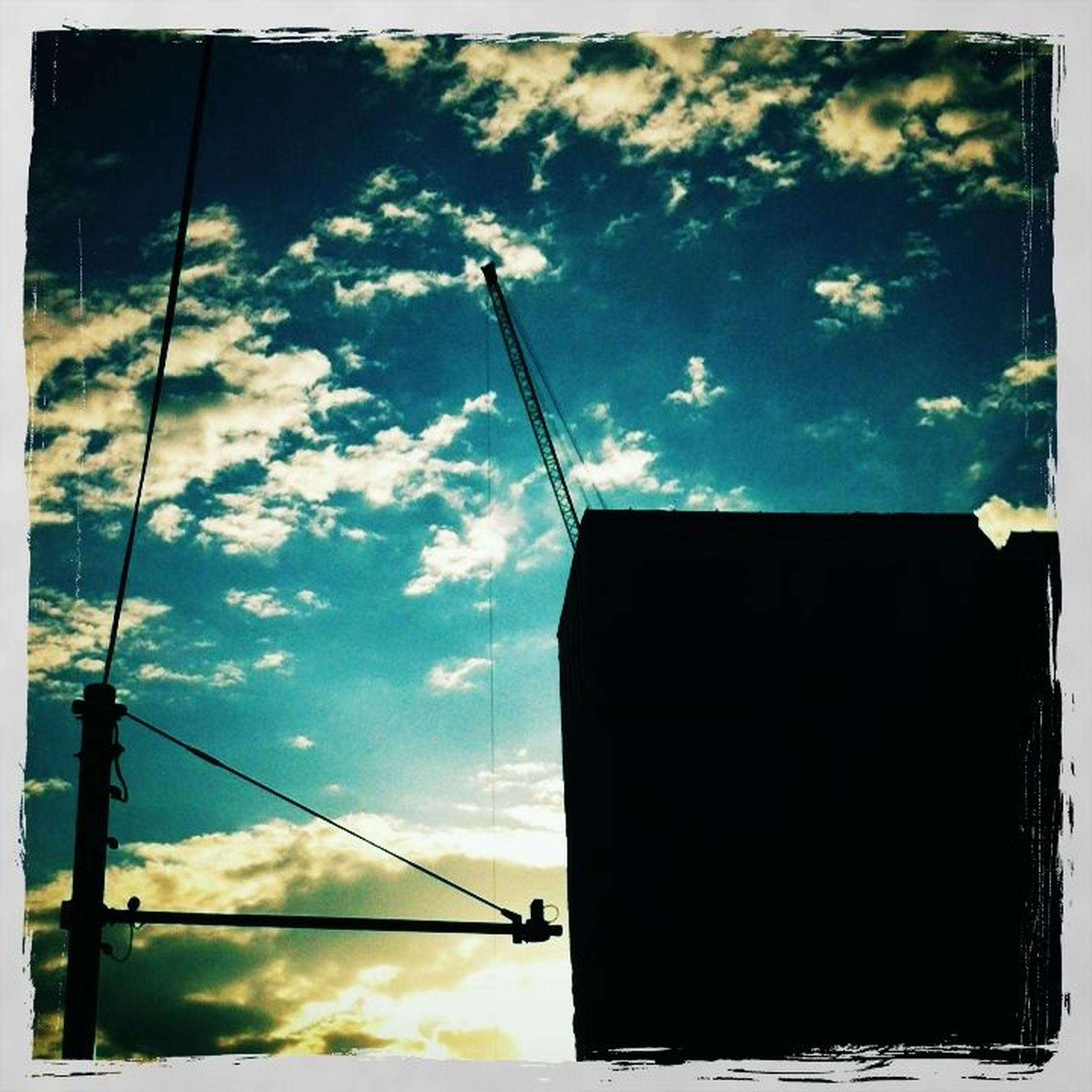 low angle view, sky, building exterior, power line, built structure, architecture, cloud - sky, cloud, electricity, silhouette, cable, street light, technology, electricity pylon, power supply, fuel and power generation, cloudy, outdoors, no people, power cable