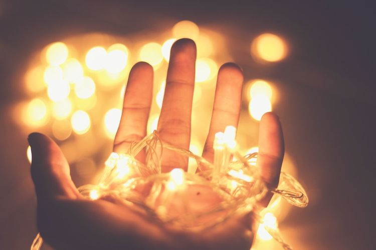 Cropped Hand Of Person Holding Illuminated String Lights At Home