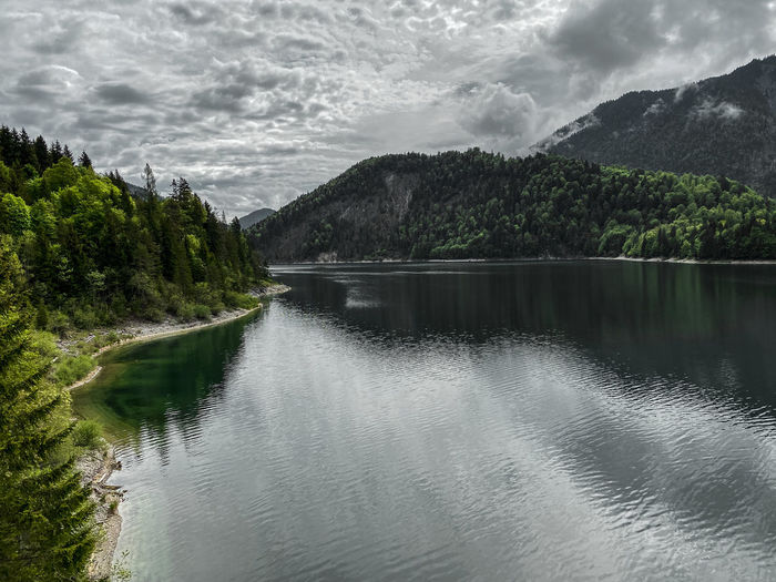 Scenic view of lake sylvensteinstausee on stormy weather against sky and mountains