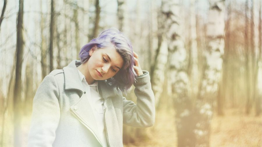 Young Woman With Dyed Hair Standing In Forest