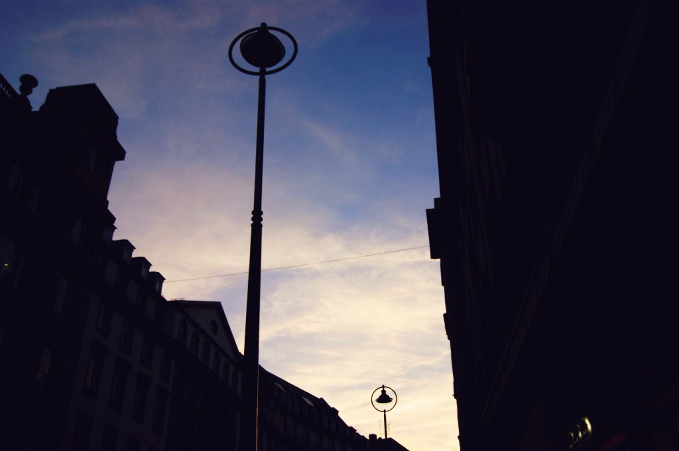 street light, low angle view, sky, building exterior, built structure, architecture, lighting equipment, silhouette, cloud - sky, cloud, pole, dusk, lamp post, building, outdoors, city, no people, electric light, electricity, cloudy