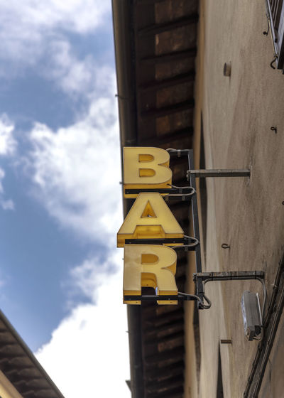 Bar Announcement Board City Entrance Sign Announcement Architecture Bare Tree Building Building Exterior Built Structure City Lights City Sights City Signs Cloud - Sky Communication Day Lighting Equipment Low Angle View Metal Pole Sign Sky Sunlight Written Yellow