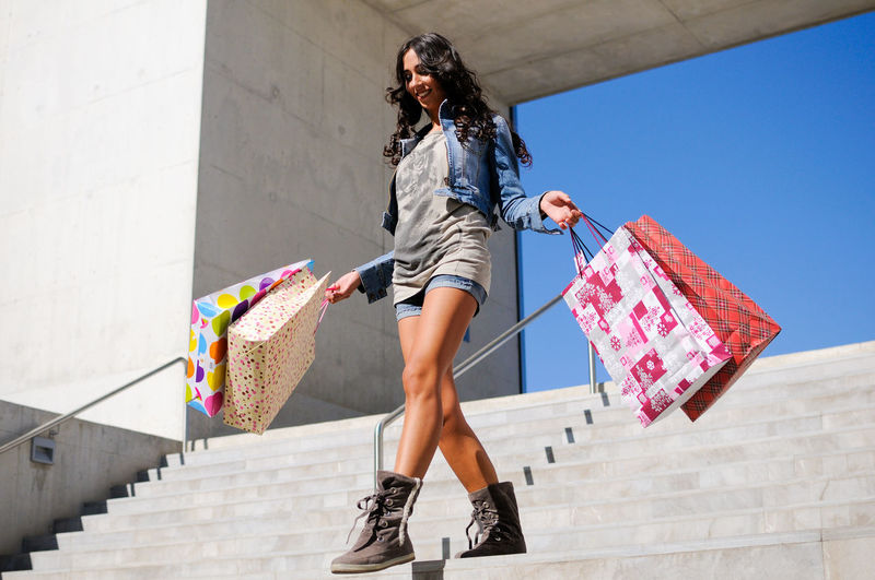 Low angle view of young woman with shopping bags walking on steps