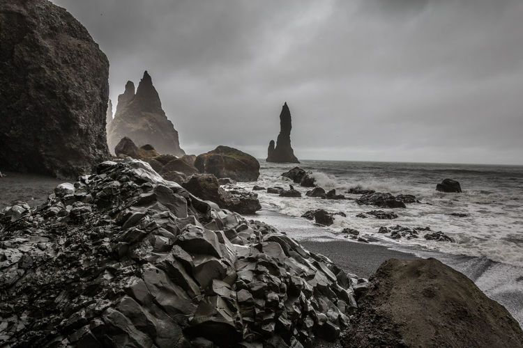 Vik Black Beach Iceland Vik Black Beach Iceland Rock Rock - Object Solid Sky Sea Water Cloud - Sky Rock Formation Beauty In Nature Beach Nature Land Scenics - Nature Tranquility Tranquil Scene Horizon Over Water Horizon No People Motion Outdoors Eroded Rocky Coastline Stack Rock