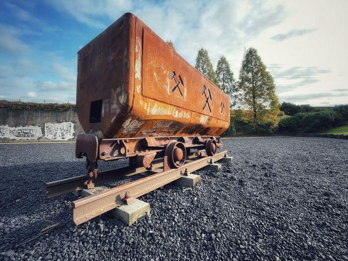 Abandoned train on railroad track against sky