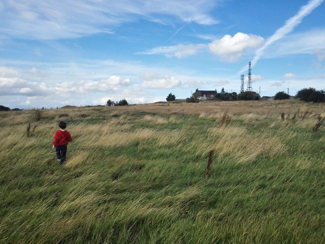 Fenton Low/fenpark/Lane Delph. Boy running across a Field with a House and Transmission Tower in the background, Blue Sky Colour Of Life