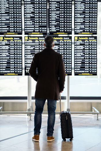Rear view of man standing at airport