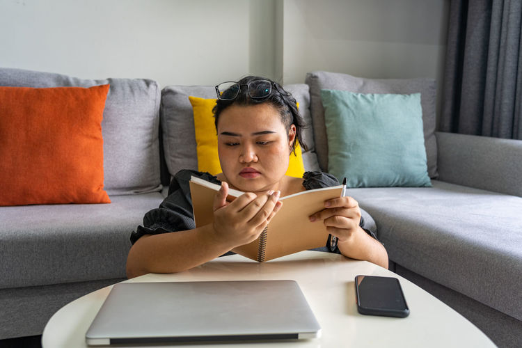 Woman reading diary while sitting at home