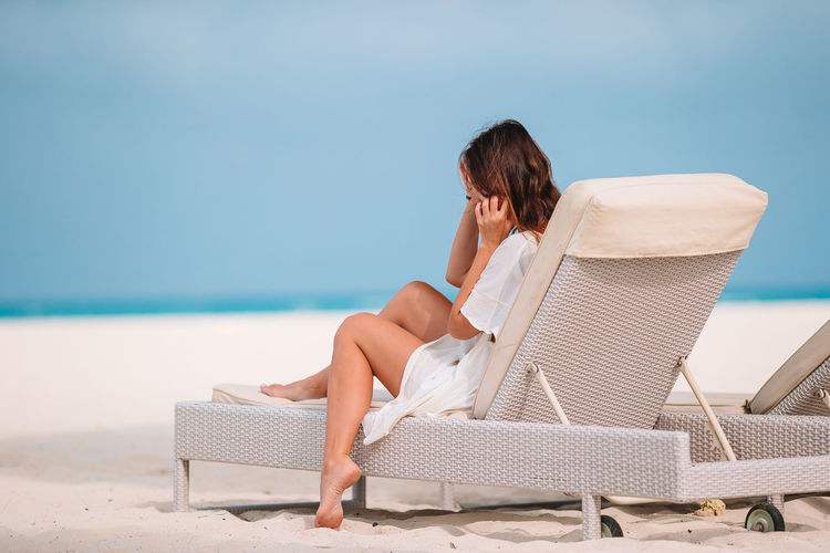 Woman sitting on chair at beach against sky