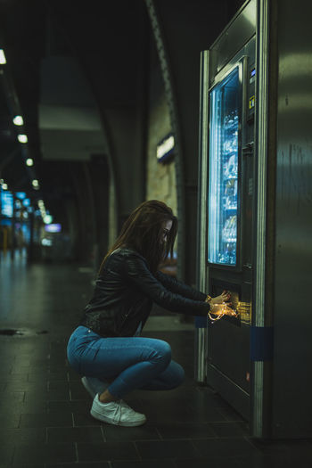 Side view of young woman holding illuminated string light opening refrigerator in store at night