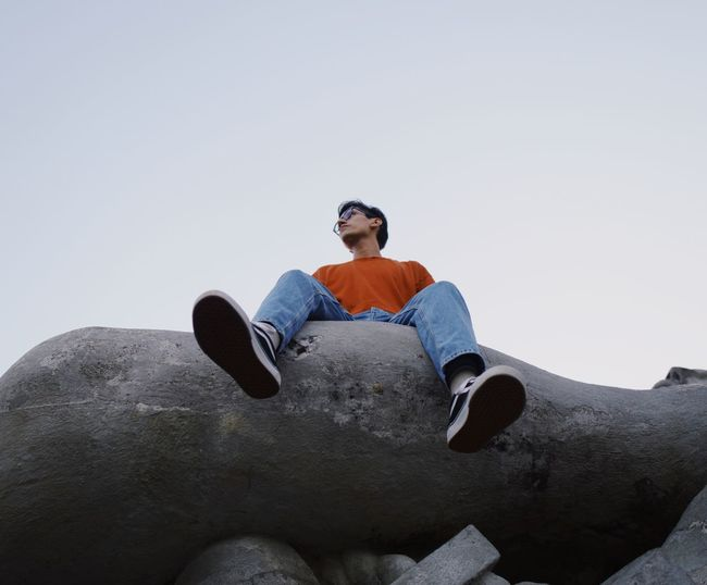 Low angle view of man sitting on rock against clear sky
