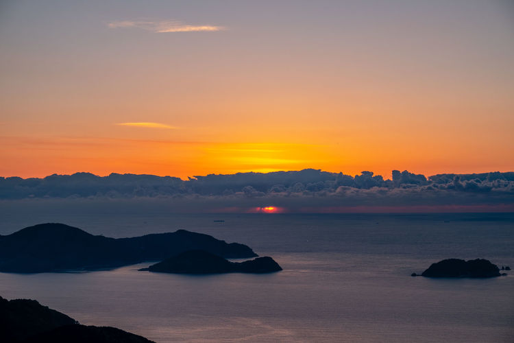 Haze and clouds layer over horizon during sunrise Sky Sunset Scenics - Nature Beauty In Nature Tranquil Scene Tranquility Sea Water Orange Color Idyllic Mountain No People Cloud - Sky Nature Non-urban Scene Silhouette Rock Outdoors Rock - Object Romantic Sky