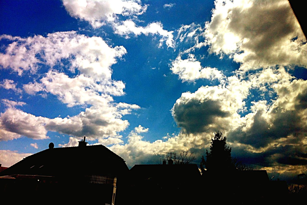 Low Angle View Of Houses Against Cloudy Sky