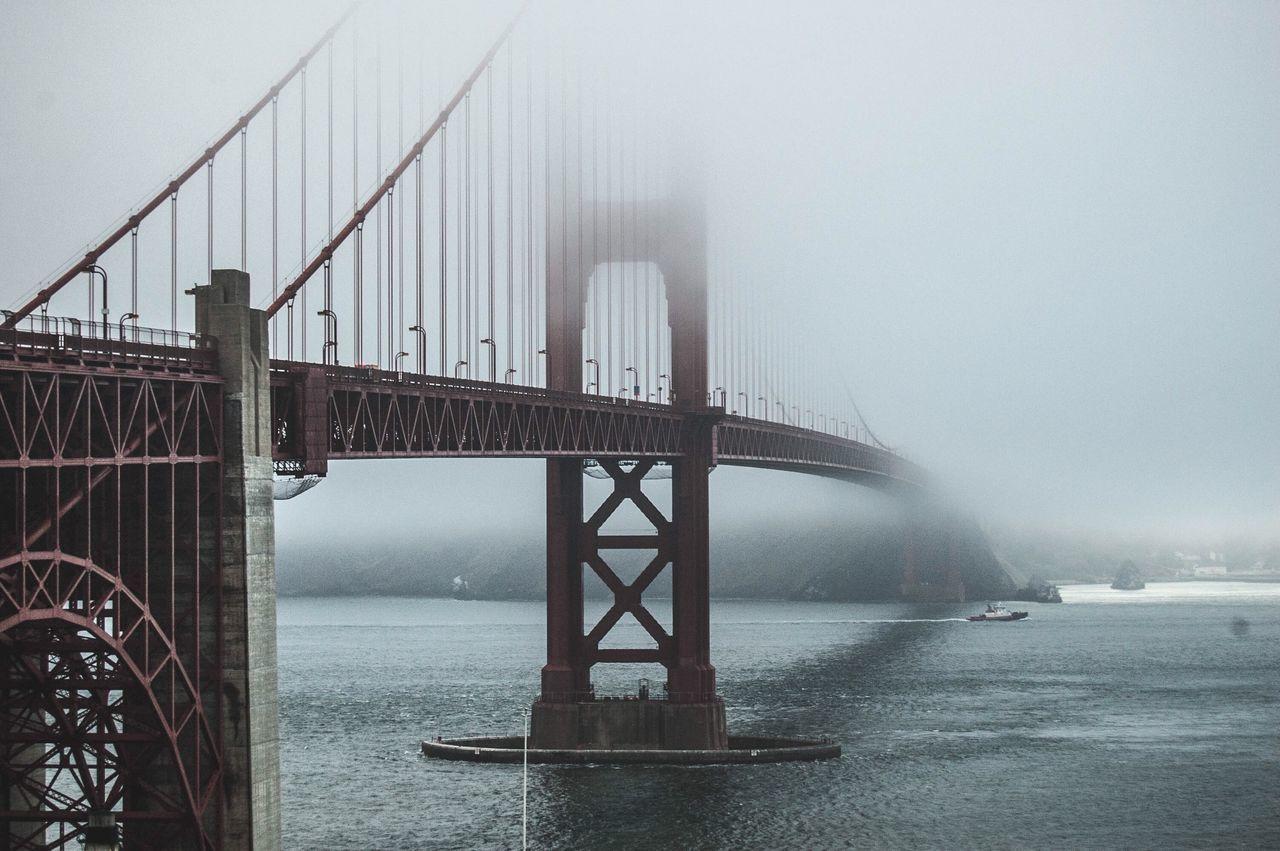 Golden Gate Bridge Over Sea Against Sky In Foggy Weather