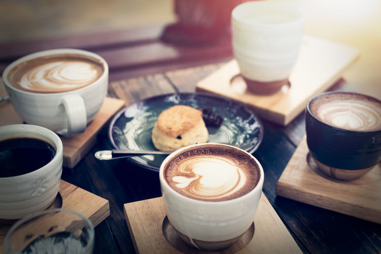 Breakfast with coffee and bread on wooden table under sunlight, vintage color tone, meeting concept.
