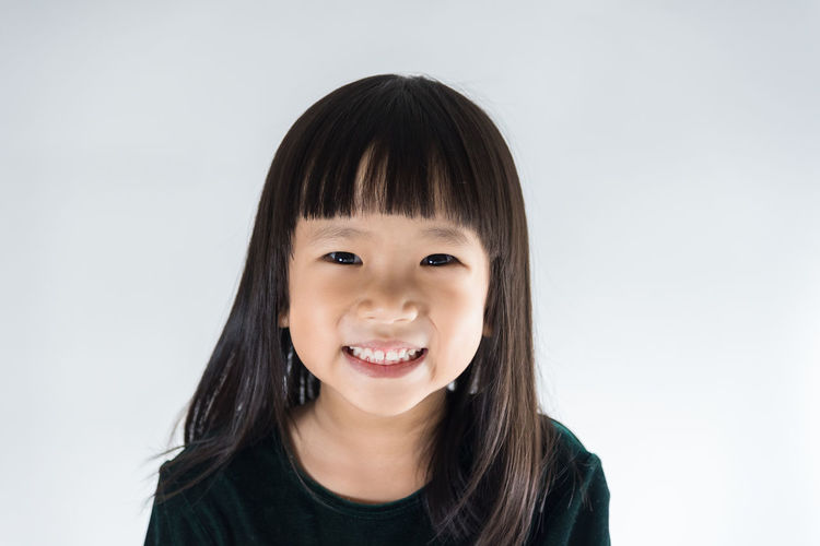 Portrait of a smiling girl against white background