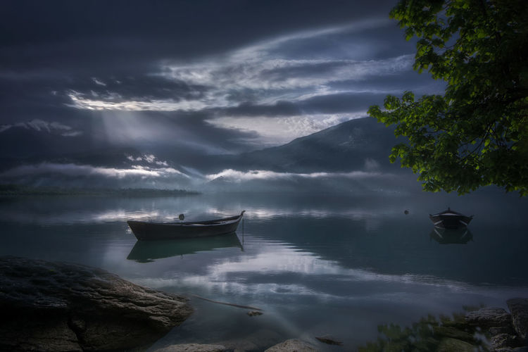 Boats moored in lake against cloudy sky