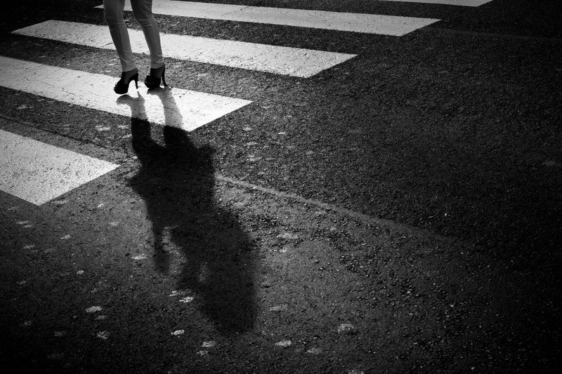 Low section of person crossing road in city