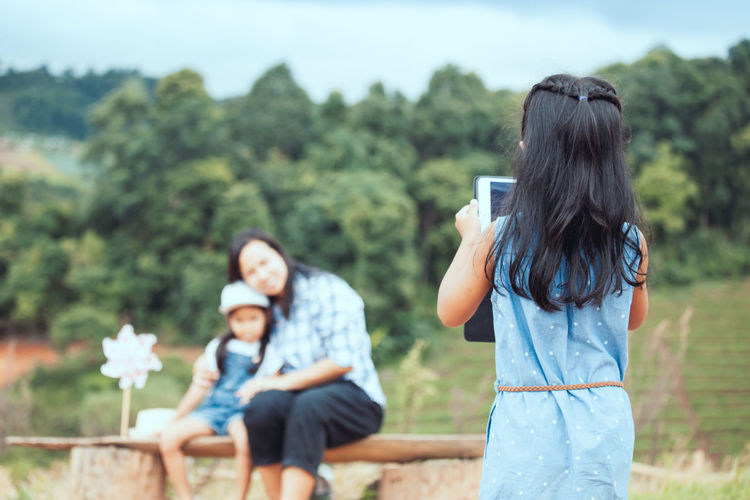 Rear View Of Girl Photographing Mother And Daughter In Park
