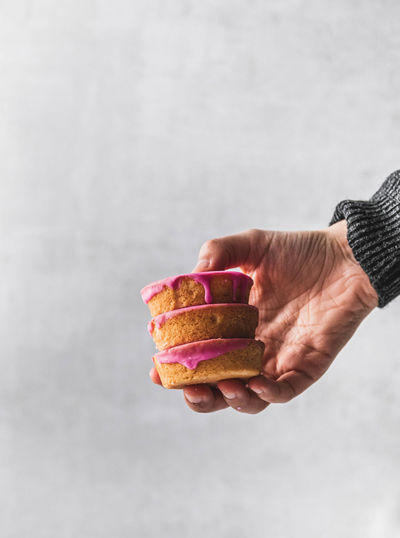 Close-up of hand holding ice cream against white background