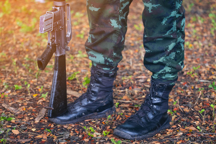 Gun on foot Army, Military Boots lines of commando soldiers in camouflage uniforms Thailand Low Section Human Leg Shoe Body Part Human Body Part Standing Day Boot Land One Person Human Limb Limb Forest Nature Autumn Outdoors Focus On Foreground Real People Tree Rubber Boot Human Foot Jeans Military