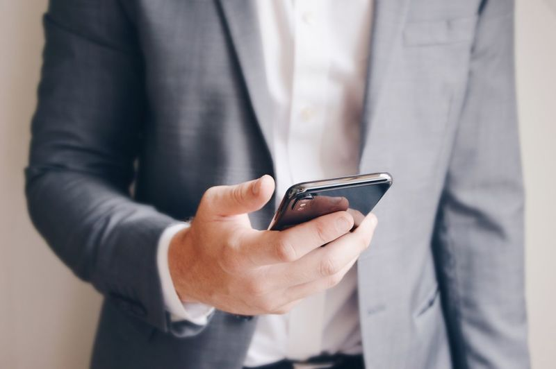 Midsection of businessman using phone