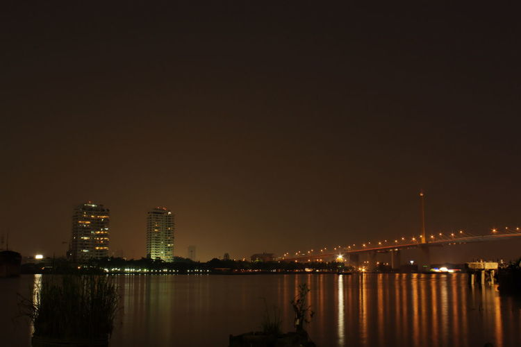 Illuminated city by river against clear sky at night