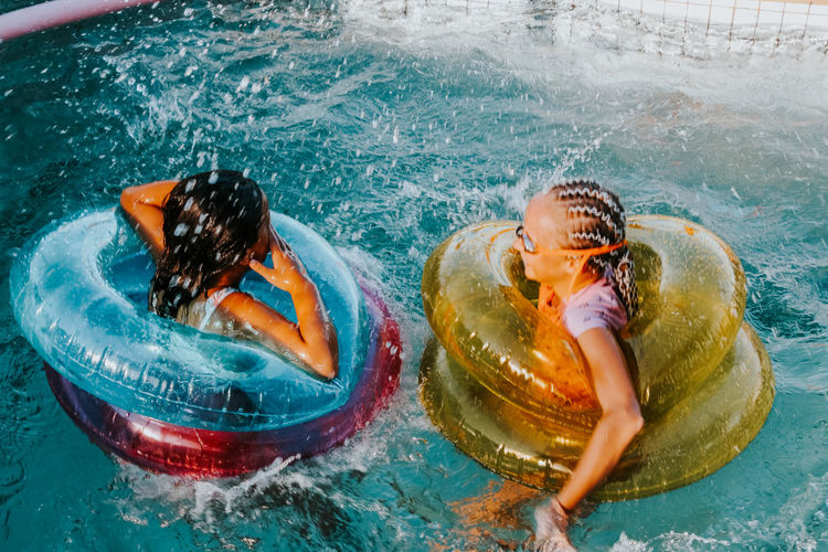 Portrait of girls with inflatable rings swimming in pool