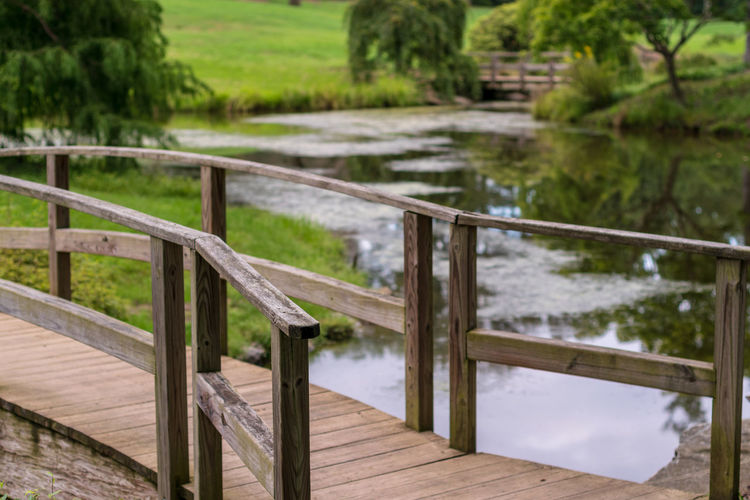 Absence Beauty In Nature Day Empty Focus On Foreground Footpath Garden Grass Green Color Nature No People Outdoors Park Plant Railing River Tranquil Scene Tranquility Tree Water Wood - Material
