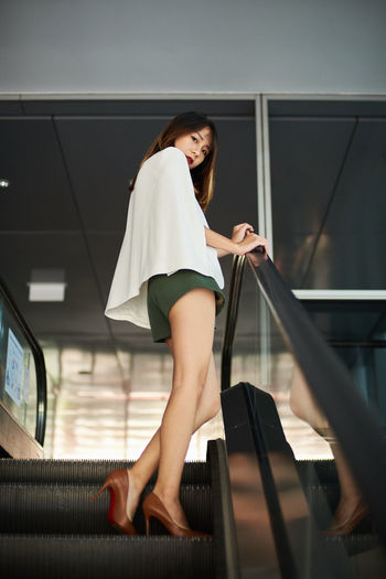 Low angle portrait of young woman standing on escalator