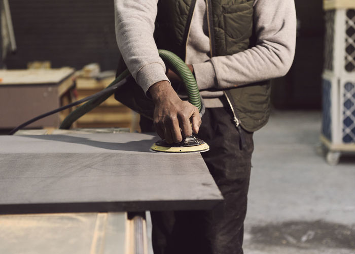 Midsection of carpenter working at workshop