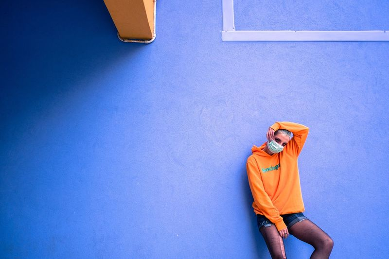Midsection of person standing against blue wall