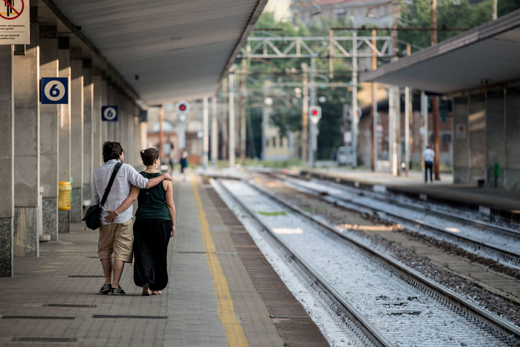 Rear View Of Couple Walking At Railroad Station Platform