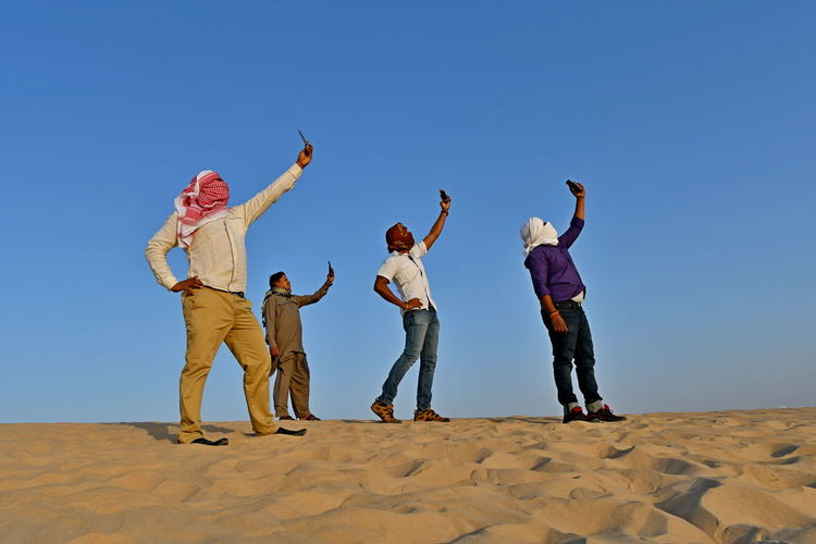 Men with covered face taking selfie while standing on sand at beach