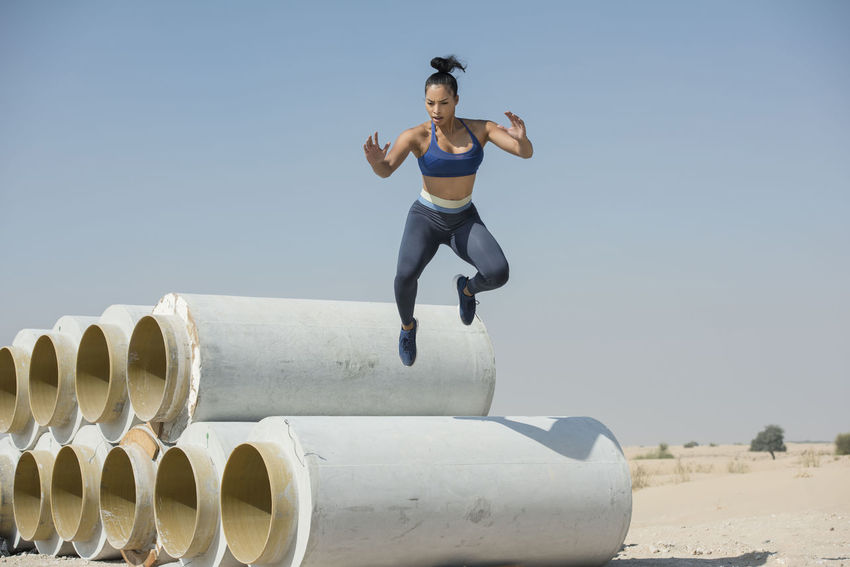 Black African American athletic woman jumps over and leaps from construction pipes wearing sports outfit in a parkour or extreme fitness competition Athlete Athletics Black Woman Parkour And Free Running African American Woman Construction Pipes Day Desert Landscape Fitness Training Full Length Jumping Leaping One Person Outdoors People Real People Skills  Sky Young Adult Young Women