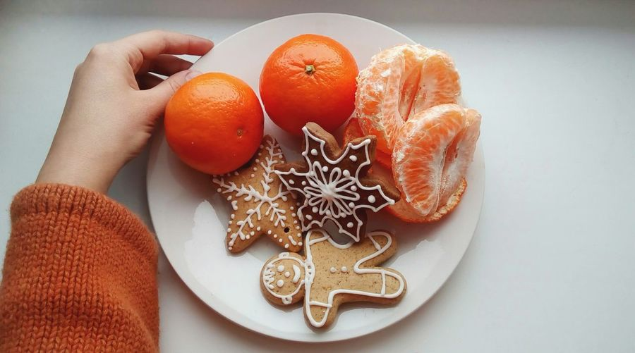 High angle view of hand holding gingerbread cookies and orange fruits in plate