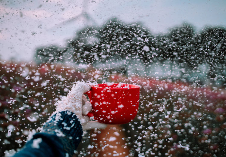 Cropped hand holding red cup while catching snow during snowfall